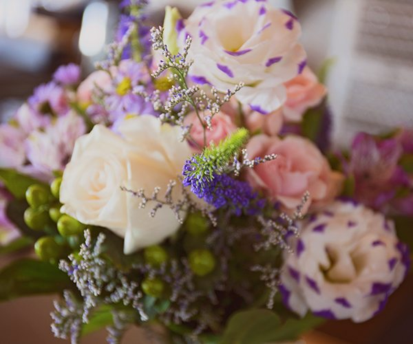 The maid of honor had a beautiful bouquet that complimented her lilac dress.
